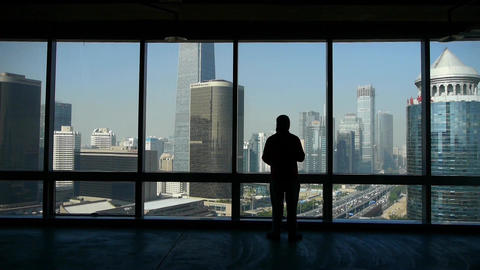 a businessman outlook business building from window Stock Video Footage