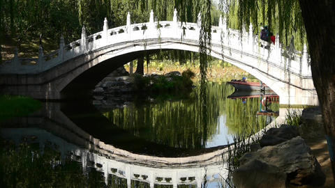 Arch bridge on lake & boat in Yuanmingyuan Park Beijing Footage