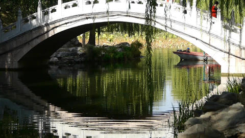 Arch bridge on lake & boat in Yuanmingyuan Park Beijing Stock Video Footage