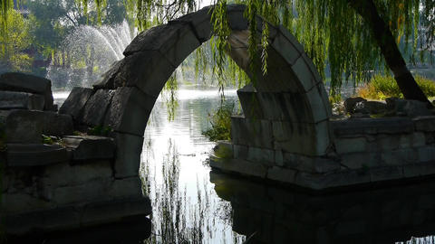 Arch bridge on lake & fountain in Yuanmingyuan Park... Stock Video Footage