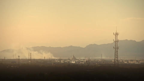 Panoramic of city town & factory smoke rely on mountain,Tower on hill at dus Footage