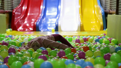 The girl lies in a pile of balls at an entertainment park Live Action