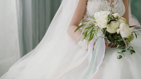 Beautiful bridal bouquet in hands of bride dressed in white wedding dress Live Action