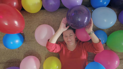 Older woman plays with air balloons while lying on sofa. She feels joy. Shot top Live Action