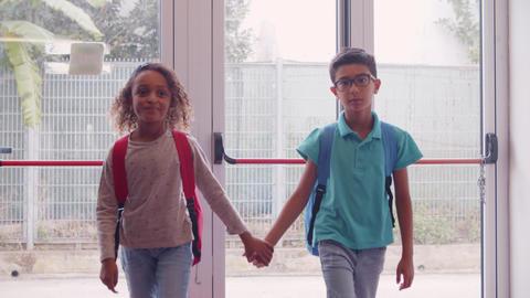 Diverse school friends walking in school corridor Live Action
