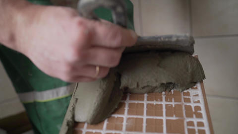 Master in overalls puts ceramic tiles on the wall. The master puts tiles on the Live Action