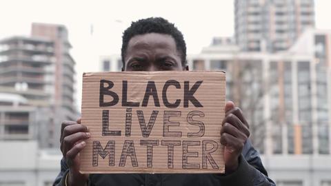 African american man hands hold poster Black Lives Matter. Sad eyes of black guy Live Action