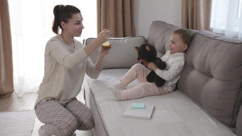 Woman feeding child with spoon. Mom feed baby with pureed food Live Action