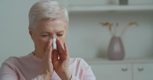 Portrait unhealthy senior old woman mature lady suffering from runny nose using Live Action