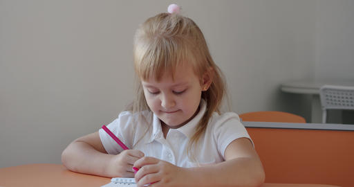Portrait school kid siting on table doing homework, school and home schooling Live Action