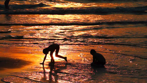 Two Kids Playing On The Beach At Sunset stock footage