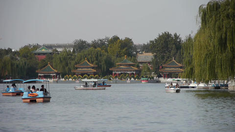 People boating on lake at China Beijing Beihai Park relying on willow island Footage