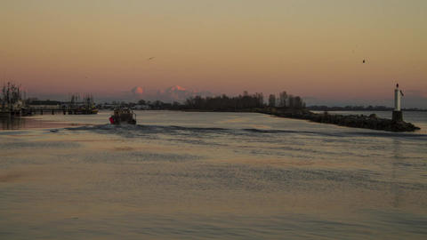 Boat arriving at Sunset times by the ocean Stock Video Footage
