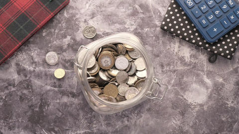 pouring coins into a jar on table top down Live Action