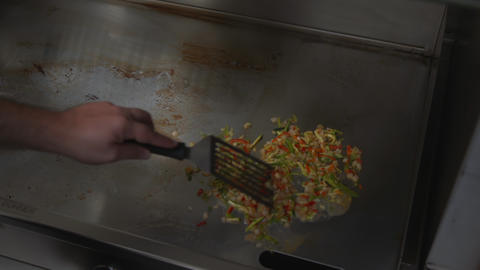 Cook separating boiling vegetables on a hot plate with a spatula. Chef cooking Live Action