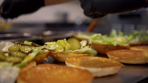 Preparing burgers in a fast food restaurant. Close up view of a fast food worker Live Action