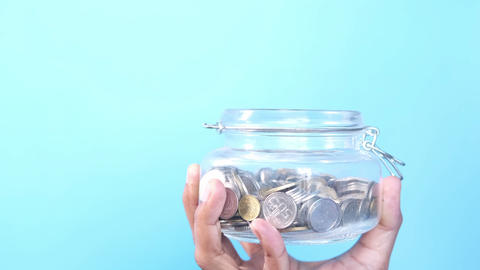coins falling into a jar against blue background Live Action