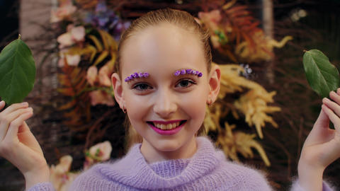 Smiling girl with green leaves front eyes with flowers makeup. Happy girl with Live Action