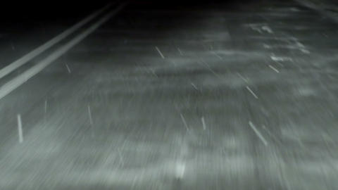 Driving a car during snowfall at night. View at the road Footage