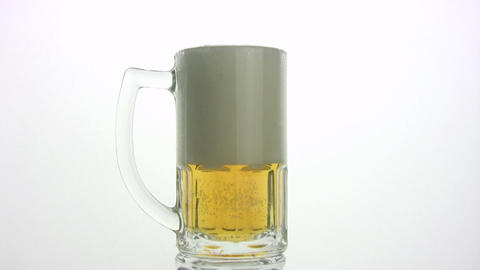 The beer is poured in a mug. White background Footage