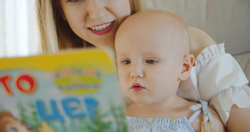 Portrait mom and child read a book before bedtime child Close up Live Action