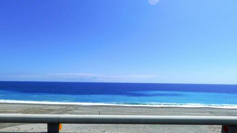 POV-Passenger side window driving scene. blue ocean against blue sky Live Action