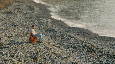 A man rests on a deserted cool beach. An introvert rest Plaid and a folding Live Action