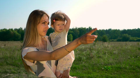 Mother Holding Child On Hands Talking To Child Pointing Finger Showing Something Summer Field Forest Live Action