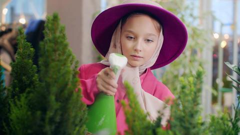 Cute girl in pink hat spraying plants in indoor garden orangery. Florists girl Live Action
