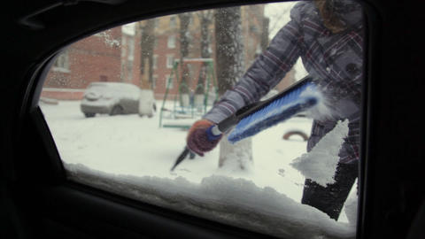 Car In Snow, Woman Cleans Snow From Car stock footage
