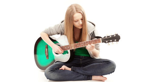 Guitarist, Girl playing a guitar while sitting on the... Stock Video Footage