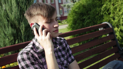 serious young man talking on the phone in park Stock Video Footage