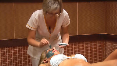 Woman puts a mud face mask Stock Video Footage