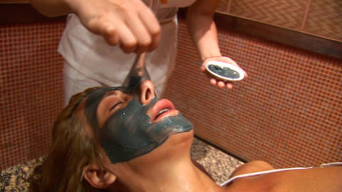 Woman puts a mud face mask b