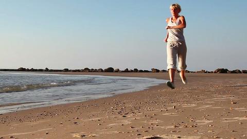 Girl jogging along a Beach Footage