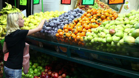 Woman chooses vegetables at the market Stock Video Footage