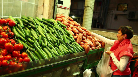 Woman chooses vegetables at the market Footage