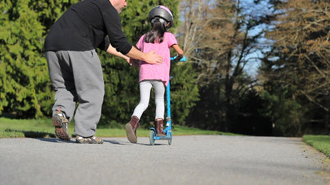 Proud Dad Helps Daughter Ride Scooter With Helmut Stock Video Footage