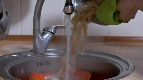 Female Drains Water from Cooked Pasta in Colander. Female Hands Open Water Tap Live Action