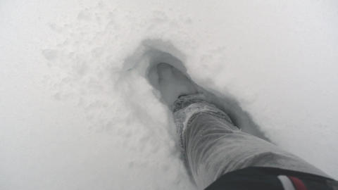 Feet are walking through very deep snow. With each step, the shoes sink deep Live Action
