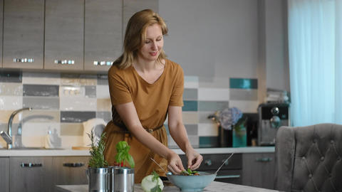 portrait of woman hold fresh salad Rbbro. add fresh growing basil leaf to Live Action