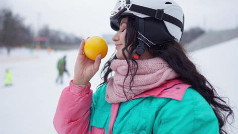 Side view of happy beautiful woman smelling healthful orange in slow motion Live Action