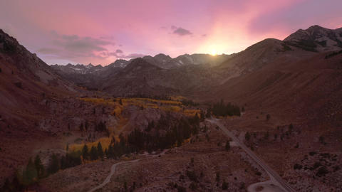 Cinematic view of scenic pink sunset sky above the high summit snowy peaks Live Action