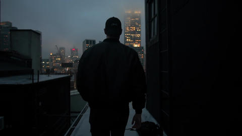 Back view of man walking on the rooftop in New York City at night. New York City Live Action