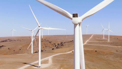Large wind turbines with blades in field aerial view, blue sky, wind park slow Live Action