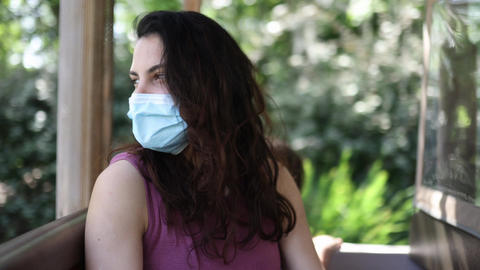Beautiful brunette woman wearing a face mask in moving vehicle Live Action