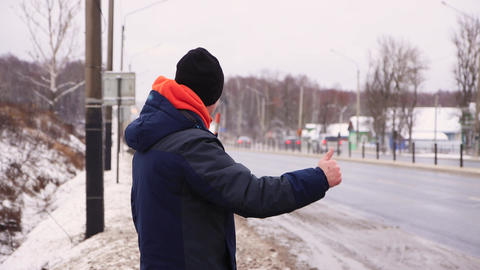 A travel man catches a passing vehicle, raises his hand Live Action