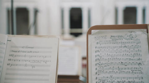 Close up focus pull of note sheets on music stands in concert hall Live Action