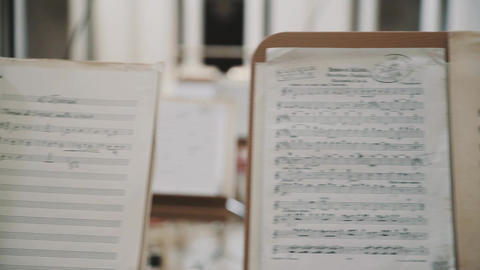 Dolly shot close up of note sheets on music stands on scene in concert hall Live Action