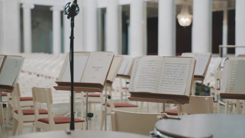Dolly shot of note sheets on music stands on scene in concert hall Live Action